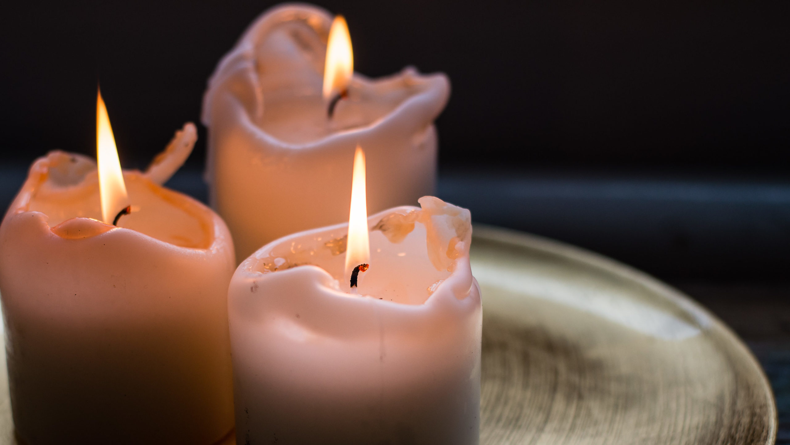 entzündete Kerzen auf goldener Auflage